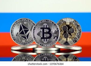 Physical version of Ethereum (ETH), Bitcoin (BTC), Ripple (XRP) and Russia Flag. The Top 3 Cryptocurrencies by Market Cap.