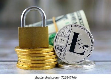 Physical version of Litecoin (new virtual money), golden padlock and banknotes of one dollar. Conceptual image for money and cryptocurrency security.