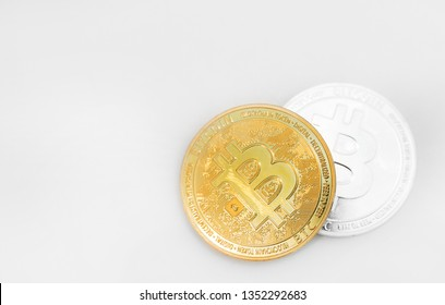 Physical version of silver and golden bitcoins on white background.