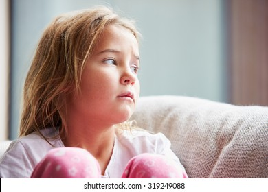 Physically Abused Child At Home Sitting On Sofa