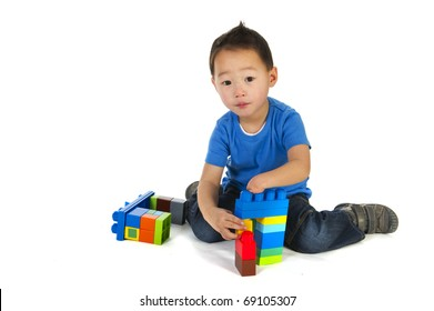 Physically disabled little boy with one hand is playing with colorful blocs