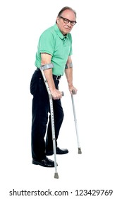 Physically disabled old man walking with the help of crutches, looking depressed