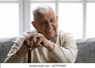 Physically disabled positive old grandfather seated on couch resting at home holding in palms walking stick smiling looking at camera. Wide toothy smile advertisement of dental services clinic concept