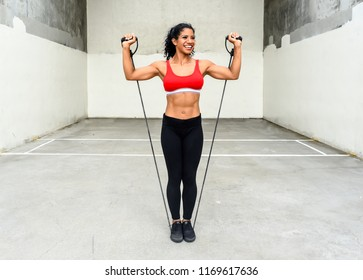 Physically fit female does a strength training exercise with resistance bands