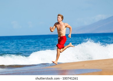 Physically fit man running on Beach