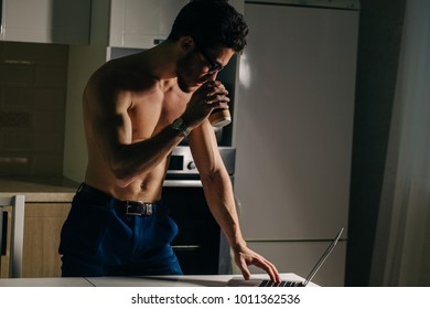 Physically Fit Man Using Laptop and drink coffee at morning