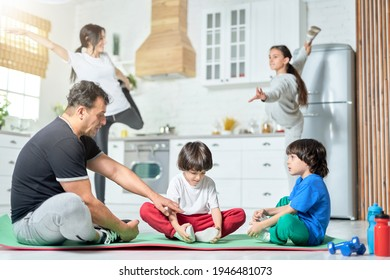 Physically fit. Two little boys sitting on a mat, practicing yoga with father while their mom and sister exercising in the background