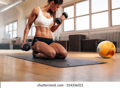 Physically fit woman at the gym lifting dumbbells to strengthen her arms and biceps. Muscular woman sitting on exercise mat looking at her arms.
