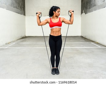 Physically fit woman works out with resistance bands