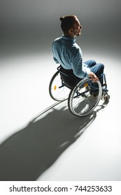 physically handicapped man in wheelchair with shadow on white floor