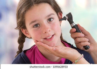 physician checking patient's ear using otoscope