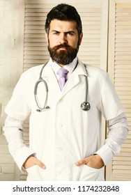 Physician with confident face ready to diagnose. Medical education and examination concept. Man in surgical uniform with stethoscope on neck on wooden background. Doctor in white medical coat
