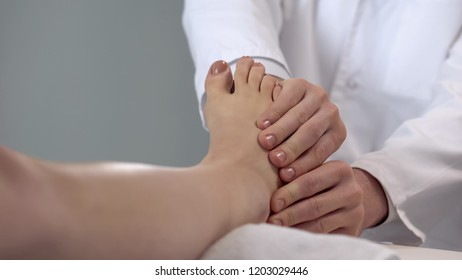 Physician examining patient foot, assessment of injury severity, healthcare