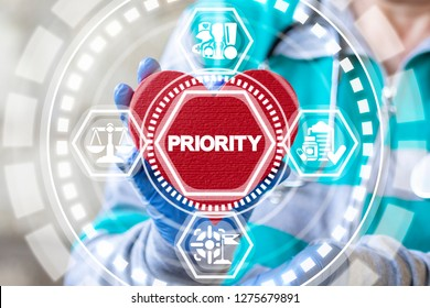 Physician holds a red heart with priority word on a virtual modern screen. Priorities time management healthcare work concept.