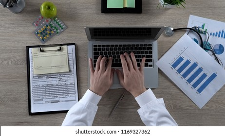 Physician looking at statistics chart, typing on laptop, preparing presentation
