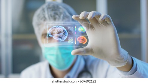 A physician, surgeon, examines a technological digital holographic plate represented , the brain of patient, . Concept: Futuristic medicine, the human body, and the future,brain