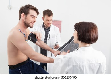 Physician taking a male patients blood pressure during a routine medical check up as a nurse explains the readout on the monitor attached by sensors to his chest in a healthcare concept