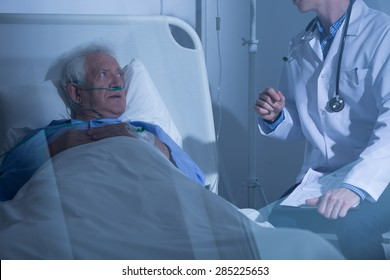 Physician talking with sick elderly man about treatment