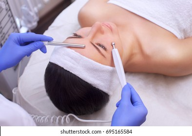 The physician-cosmetologist makes Electric Facial Treatment of the skin of a beautiful, young woman in a beauty salon. Cosmetology and professional skin care.