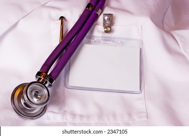 Physician's white labcoat with blank name badge, pen, and stethoscope.
