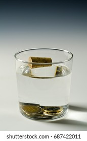 Physics. A cork floats in water and metal coins sinks. Archimedes principle.