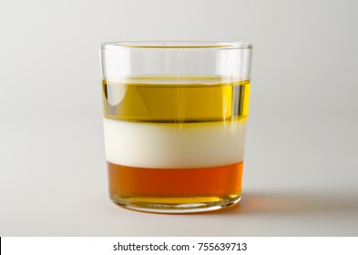 Physics. Density column. Laboratory glassware containing separed layers of vegetable oil, milk and honey.