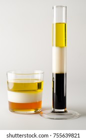 Physics. Density column. Laboratory glassware containing separed layers of vegetable oil, milk and maple syrup.