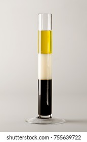 Physics. Density column. Test tube containing separed layers of vegetable oil, milk and maple syrup.