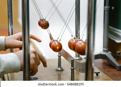 Physics experiment with cradle balls in laboratory. Research concept. Conservation of energy. Simple Pendulum, moving towards the main position the potential energy is converted to kinetic energy.