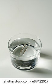 Physics. Surface tension. A paper clip floating on water.