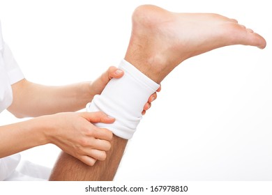 Physioterpist putting an elastic band on injured leg of patient