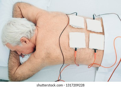 Physiotherapeutic treatment. Senior patient having ultrasound and electrotherapy treatment on his back