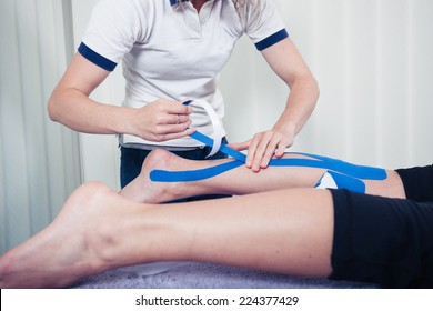 A physiotherapist is applying kinesio tape to a patient's leg