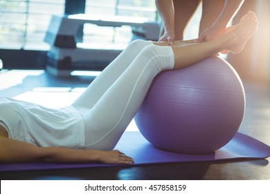 Physiotherapist assisting a patient with exercise ball in clinic