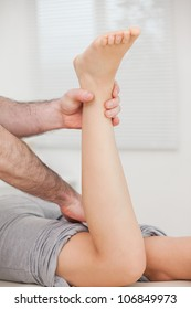 Physiotherapist bending the leg of a patient in a room