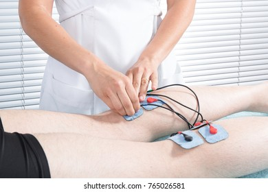 Physiotherapist branch electric electrodes on the legs of a sporty man