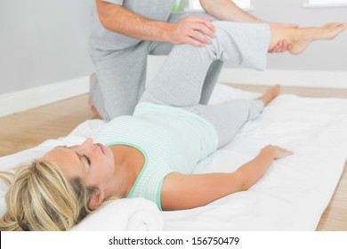 Physiotherapist checking patients leg on a mat on the floor in bright room