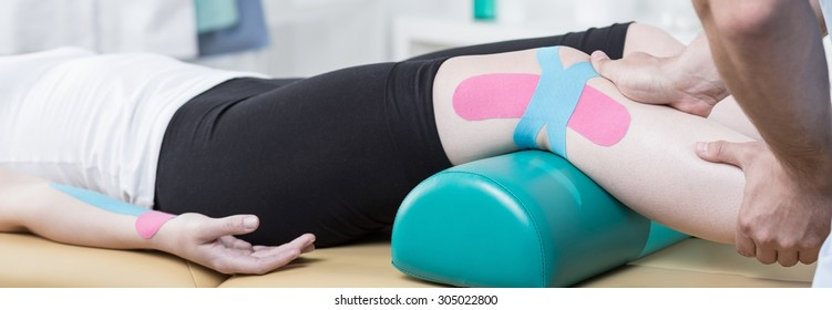 Physiotherapist is conducting leg rehabilitation on his patient