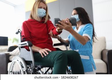 Physiotherapeut Arzt in der medizinischen Maske hilft, eine Hantel für behinderte Frau im Rollstuhl zu Hause Porträt zu erhöhen. Rehabilitation behinderter Menschen zu Hause während Epidemien- und Coronavirus-Infektionen