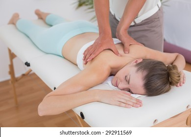 Physiotherapist doing back massage to his patient in medical office