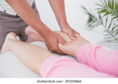 Physiotherapist doing calf massage in medical office
