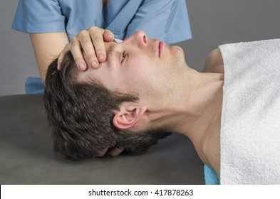 Physiotherapist doing a cranial sacral therapy to a man patient.