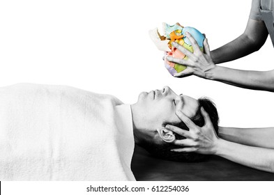 Physiotherapist doing a cranial sacral therapy to a man patient and another physiotherapist with a fake skull showing  position of the hands in silhouette studio on white backgroun.