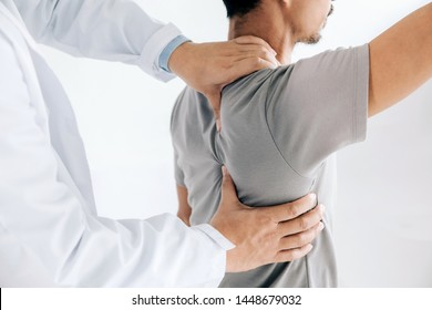 Physiotherapist doing healing treatment on man's back.Back pain patient, treatment, medical doctor, massage therapist.office syndrome