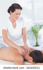 Physiotherapist doing neck massage to her patient in medical office