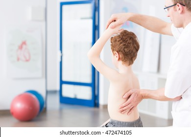 Physiotherapist during exercises with boy, light interior
