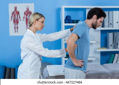 Physiotherapist examining mans back in clinic