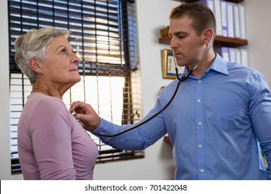 Physiotherapist examining patient with stethoscope in clinic