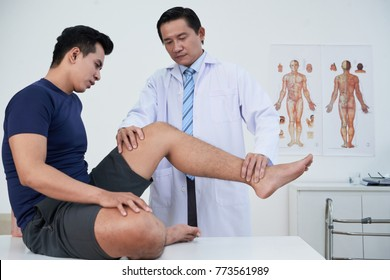 Physiotherapist examining young sportsman with trauma of leg