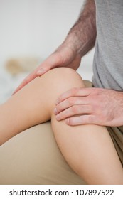 Physiotherapist folding a leg over her thigh in a physio room